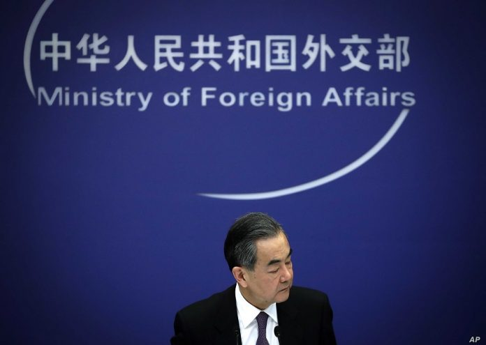 Chinese State Councilor and Foreign Minister Wang Yi reacts during a news conference at the Ministry of Foreign Affairs in Beijing